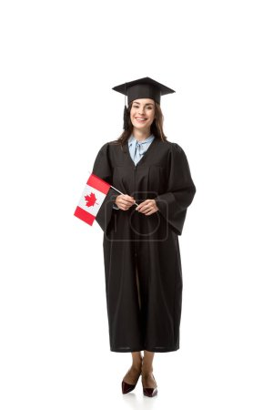 beautiful smiling female student in academic gown holding canadian flag isolated on white