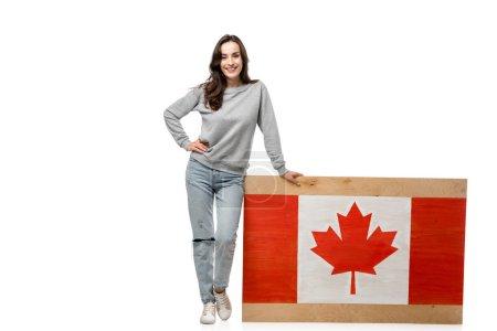 Photo pour Femme souriante avec la main sur la hanche debout près de planche de bois avec le drapeau canadien isolé sur blanc - image libre de droit