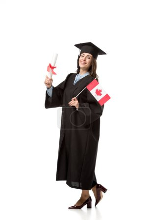 happy female student in academic gown holding canadian flag and diploma isolated on white