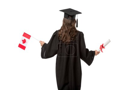 back view of female student in academic gown and mortarboard holding canadian flag with diploma isolated on white