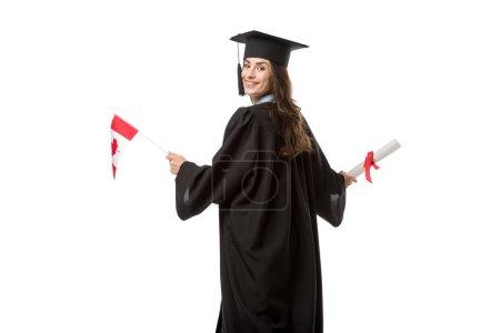Foto de Atractivo estudiante sonriente en vestido académico sosteniendo la bandera canadiense y diploma aislado en blanco - Imagen libre de derechos