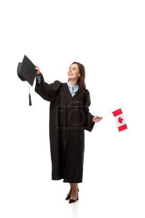 étudiante en robe académique tenant le drapeau canadien et mortier isolé sur blanc