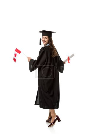 smiling female student in academic gown holding canadian flag and diploma isolated on white