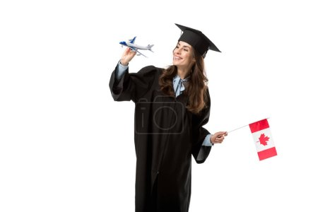 happy female student in academic gown holding canadian flag and plane model isolated on white, studying abroad concept