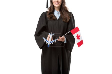 cropped view of female student in academic gown holding canadian flag and plane model isolated on white, studying abroad concept