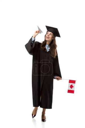 cheerful female student in academic gown holding canadian flag and paper plane isolated on white