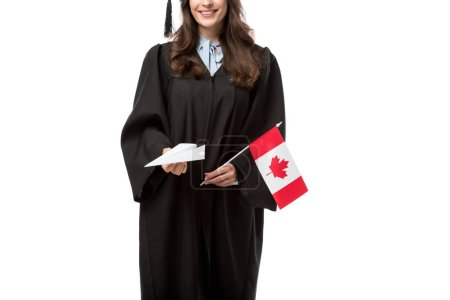 cropped view of female student in academic gown holding canadian flag and paper plane isolated on white