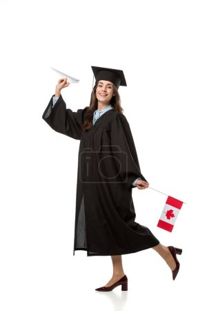 happy female student in academic gown holding canadian flag and paper plane isolated on white