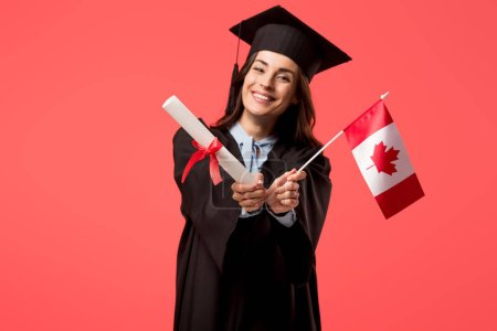 Photo for Smiling female student in academic gown holding canadian flag isolated on living coral - Royalty Free Image