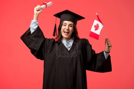 female student in academic gown holding canadian flag and diploma isolated on living coral
