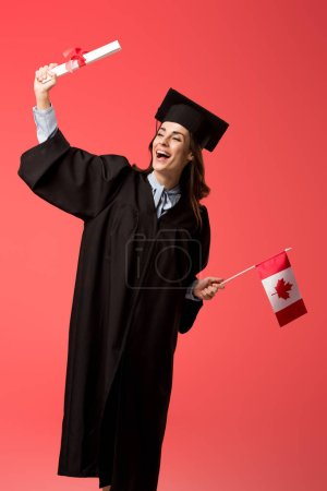 Photo for Happy female student in academic gown holding canadian flag and diploma isolated on living coral - Royalty Free Image