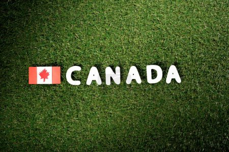Photo for Top view of word 'Canada' with canadian flag on green grass background - Royalty Free Image