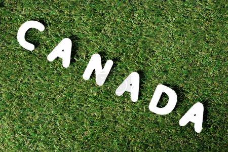 Photo pour Mot «Canada» en lettres blanches avec une herbe verte sur fond - image libre de droit