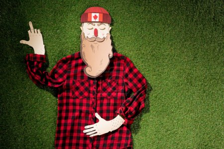 cardboard man in plaid shirt and hat with maple leaf showing middle finger on green grass background