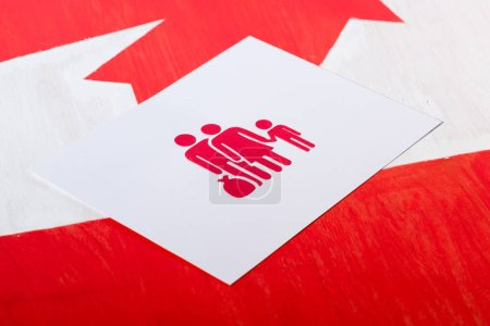 selective focus of white card with family icon on canadian flag, immigration concept