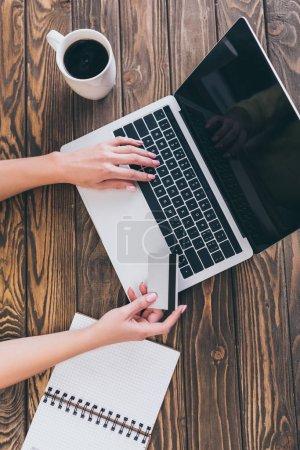 Photo pour Vue de dessus de la femme à l'aide d'ordinateur portable tout en maintenant la carte de crédit près de tasse de café - image libre de droit