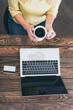 cropped view of woman holding cup of coffee near laptop and credit card
