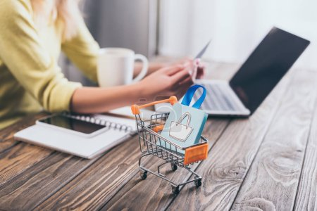 Photo for Selective focus of small shopping bag in shopping trolley with woman using laptop on background - Royalty Free Image