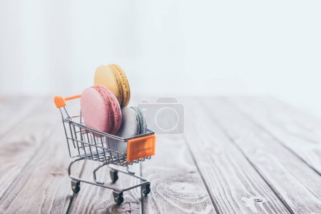 tasty macaroons in small shopping trolley on wooden table
