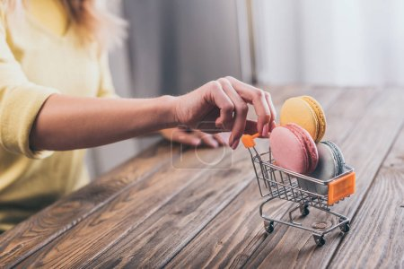 Photo for Cropped view of woman holding small shopping trolley with tasty macaroons - Royalty Free Image