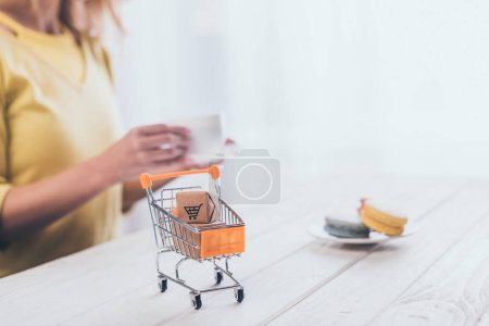 selective focus of small paper boxes in toy shopping trolley with woman on background