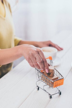 selective focus of woman putting toy paper box in small shopping trolley with cup on background