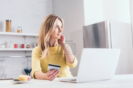 attractive blonde woman holding credit card near laptop in kitchen