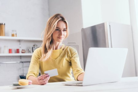 attractive woman holding credit card while using laptop