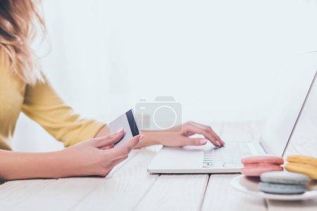Photo pour Vue recadrée de la femme en utilisant un ordinateur portable tout en tenant la carte de crédit - image libre de droit