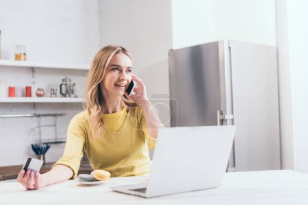 attractive woman talking on smartphone while holding credit card