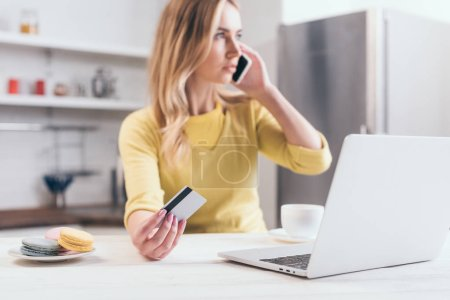selective focus of credit card in hand of blonde woman talking on smartphone