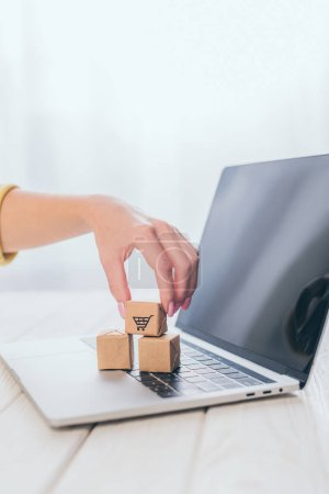 cropped view of woman putting toy paper box on laptop keyboard