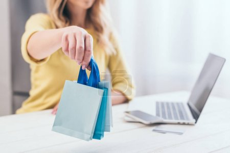 selective focus of woman holding toy shopping bags at home
