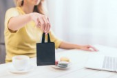 selective focus of woman holding small black shopping bag at home