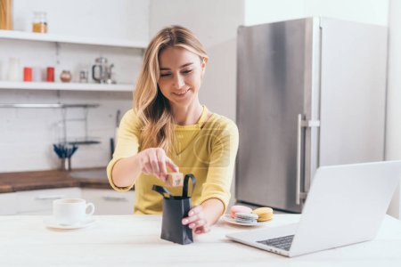 attractive woman putting small paper box into black shopping bag in kitchen