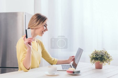 Photo for Cheerful woman holding credit card while looking at laptop - Royalty Free Image