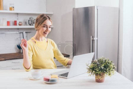happy woman holding credit card while looking at laptop in kitchen