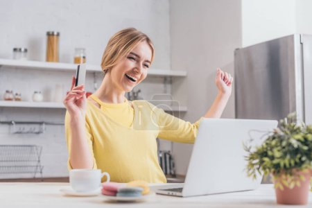 excited woman holding credit card while looking at laptop