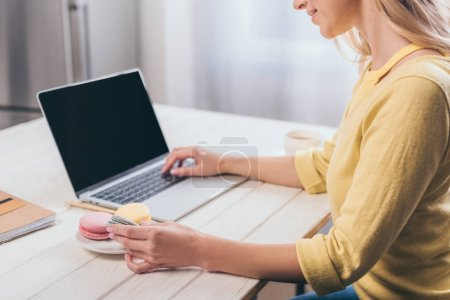 cropped view of woman typing on laptop and holding macaroon