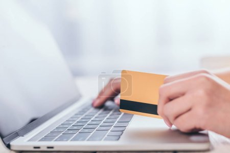 selective focus of credit card in hand of woman using laptop