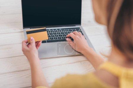 vue recadrée de la femme tenant la carte de crédit près d'un ordinateur portable avec écran blanc