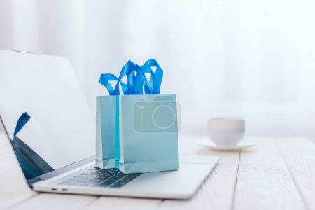 foco selectivo de bolsas de compras de juguetes en el teclado del ordenador portátil con taza en el fondo