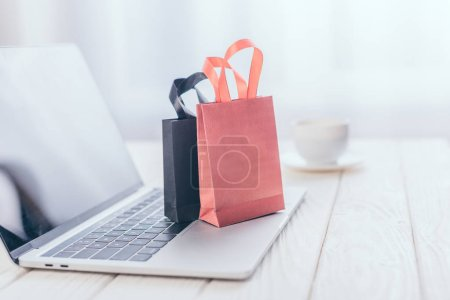 Photo for Selective focus of small shopping bags on laptop with cup on background - Royalty Free Image