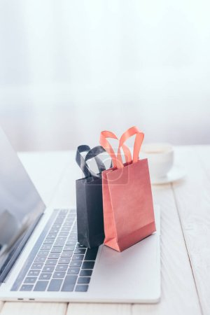 selective focus of small shopping bags on laptop keyboard with cup of coffee on background