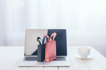 Photo pour Petits sacs à provisions sur clavier d'ordinateur portable avec tasse sur fond - image libre de droit