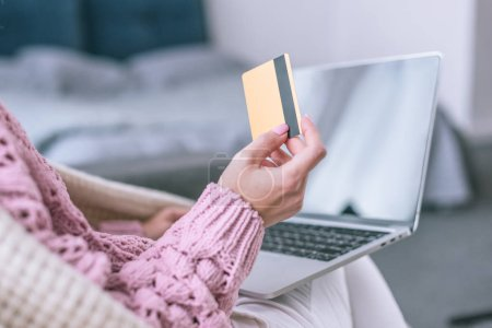 cropped view of woman holding credit card near laptop at home
