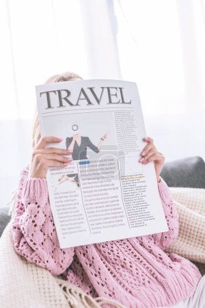 Photo for Woman reading travel newspaper while sitting at home - Royalty Free Image