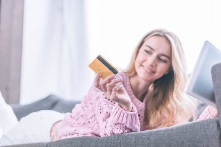 smiling woman looking at holding credit card while lying on sofa with digital tablet