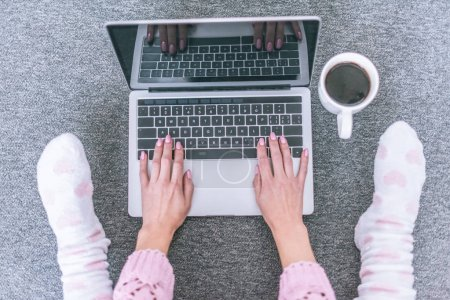 top view of female blogger typing on laptop keyboard near cup of coffee