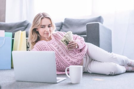 cheerful woman looking at laptop while holding dollar banknotes at home